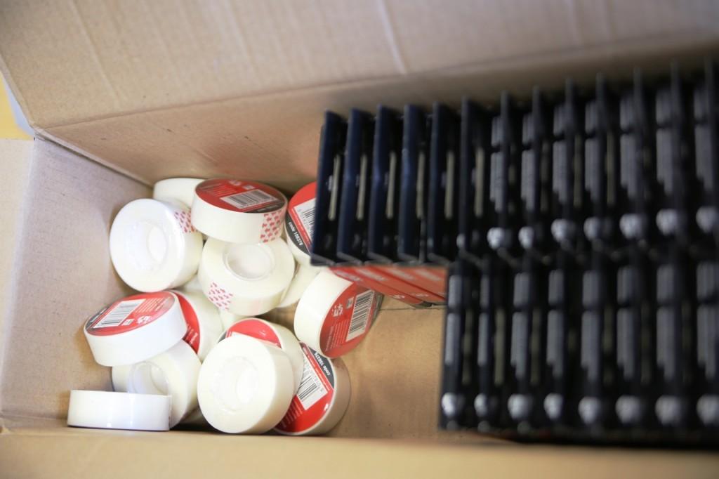 Transparante sticky tape en rekenmachientjes in een doos