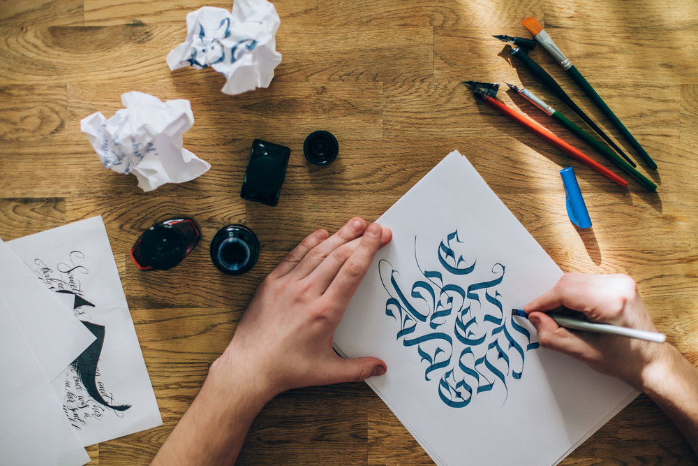 Hands designing calligraphy text