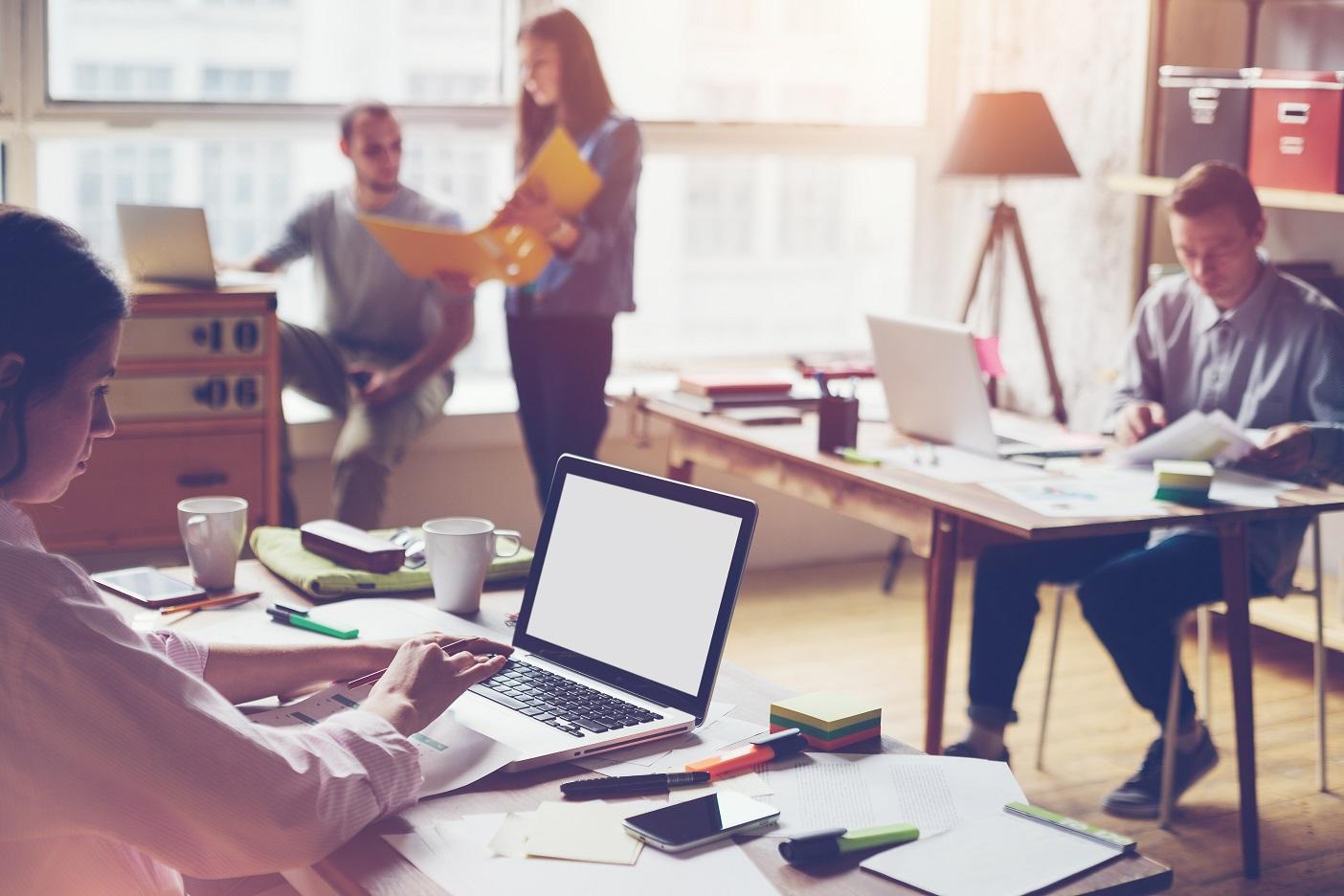 Millennials werkend op kantoor achter laptop