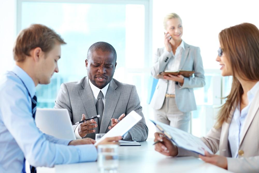 Drie collega's houden een vergadering achter een bureau